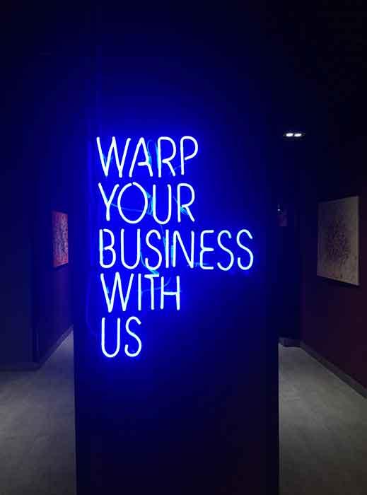 """Неоновая надпись """"WARP YOUR BUSINESS WITH US"""" в """"Креативный квартал"""" (CQ) в БЦ """"Астарта"""""""