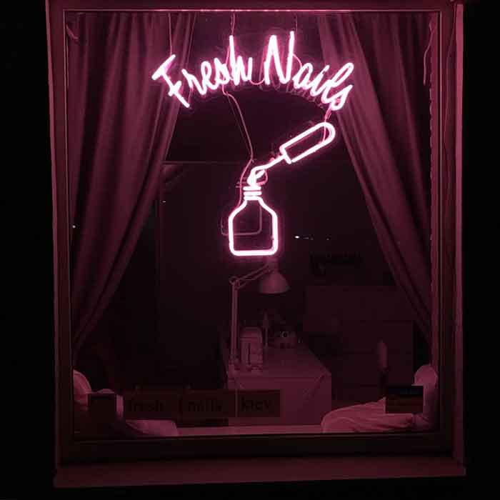 Неоновая вывеска на витрине студии маникюра и педикюра